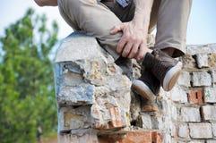 Les jambes des hommes dans le brun chausse des espadrilles Homme de hippie s'asseyant sur le vieux mur de briques extérieur Photographie stock