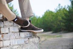 Les jambes des hommes dans le brun chausse des espadrilles Homme s'asseyant sur le vieux mur de briques extérieur Images stock