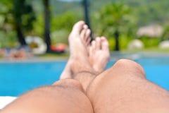 Les jambes des hommes en gros plan contre dans la piscine Image libre de droits