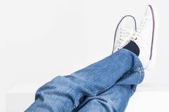 Les jambes des hommes sur les espadrilles blanches et les jeans de mode étendus sur l'appui élevé Photos stock