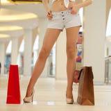 Les jambes des jeans de port shopaholic court-circuite tout en portant plusieurs p photos stock