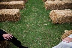 Les jambes des jeunes mariés se tiennent dans le bas-côté l'épousant qui est fait de meules de foin image libre de droits