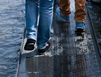 Les jambes des personnes sur le pont en métal images libres de droits