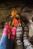 Les jambes du couple romantique dans les chaussettes devant la cheminée Photographie stock libre de droits