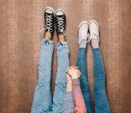 Les jambes du jeune couple de mode dans des pieds de jeans et d'espadrilles se lèvent et tenant des mains sur le mur Fin vers le  Photos libres de droits