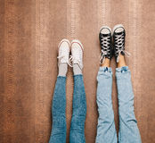Les jambes du jeune couple de mode dans des pieds de jeans et d'espadrilles sur le mur Fin vers le haut d'intérieur Couleur chaud Image libre de droits