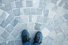 Les jambes du ` s d'hommes dans la vue supérieure d'espadrilles et de jeans sur le trottoir pavent en cailloutis Photos stock