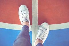 Les jambes du ` s de femmes dans des espadrilles blanches se tiennent sur le choix Image libre de droits