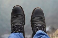 Les jambes du voyageur se reposant sur une haute montagne complètent dans le voyage Images stock