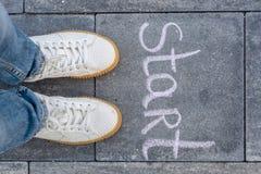 Les jambes femelles chaussées dans des espadrilles blanches et le mot démarrent Photos libres de droits