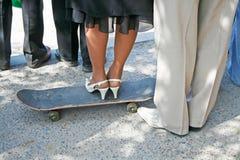 Les jambes femelles dans des chaussures élégantes blanches se tiennent sur une planche à roulettes noire et des jambes de mâle ap Image libre de droits
