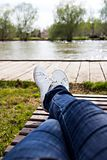 Les jambes femelles dans les jeans et des espadrilles blanches se trouvent sur une chaise longue Images libres de droits