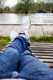 Les jambes femelles dans les jeans et des espadrilles blanches se trouvent sur une chaise longue Image stock