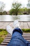 Les jambes femelles dans les jeans et des espadrilles blanches se trouvent sur une chaise longue Images stock