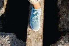 Les jambes femelles dans le pantalon et des espadrilles beiges sont sur le conseil Image stock