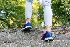 Les jambes femelles dans les espadrilles et des jeans montent les escaliers concrets dans t Images stock
