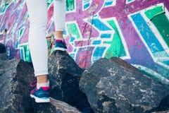 Les jambes femelles dans les espadrilles et des jeans s'élèvent au-dessus des roches sur le Ba Image libre de droits