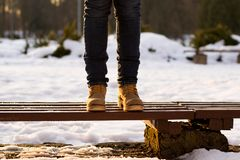 Les jambes femelles se tiennent sur le banc dans le jour ensoleillé d'hiver Fond brouillé des rayons de neige et de coucher du so images stock