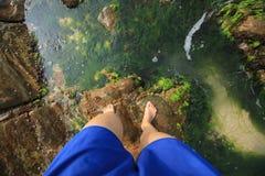 Les jambes humaines se tiennent sur la roche photo stock