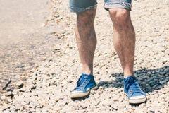 Les jambes masculines dans des espadrilles bleues de toile et le bleu ont découpé des shorts de jeans se tenant sur le Pebble Bea Images libres de droits