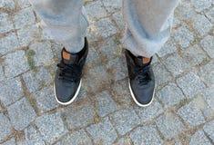 Les jambes masculines dans des espadrilles en cuir noires se ferment  Photos libres de droits