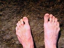 Les jambes masculines nues sur la crête font l'étape Roche de grès au-dessus de vallée avec les jambes fatiguées de randonneurs Image libre de droits