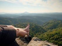 Les jambes masculines nues sur la crête font l'étape Roche de grès au-dessus de vallée avec les jambes fatiguées de randonneurs s Photo libre de droits