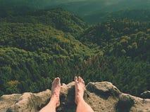 Les jambes masculines nues sur la crête font l'étape Roche de grès au-dessus de vallée avec les jambes fatiguées de randonneurs s Images libres de droits
