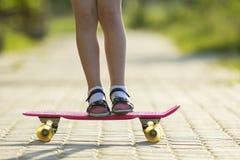 Les jambes minces de fille en chaussettes blanches et sandales noires se tenant sur le trottoir sur la planche à roulettes rose e Photos libres de droits