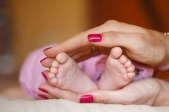 Les jambes nouveau-nées dans des mains douces de mère Photographie stock