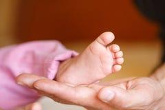 Les jambes nouveau-nées dans des mains douces de mère Photo libre de droits
