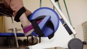 Les jambes sont ergomètre pédalant de cycle comme exercice pour la forme physique examinant dans l'hôpital clips vidéos