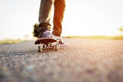 Les jambes sur la planche à roulettes ont éclairé par le soleil photographie stock