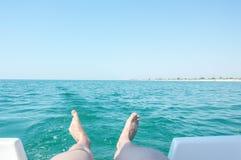 Les jambes sur un fond d'une turquoise ondulent Images stock