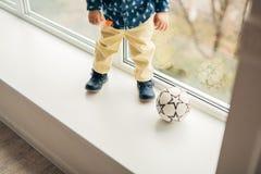 Les jambes un petit enfant jouant la boule Photographie stock libre de droits