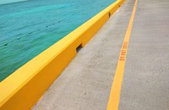 Les jaunes font pas ligne croisée sur le bord de mer photographie stock