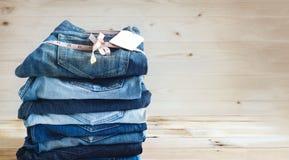 Les jeans avec la mesure et l'étiquette marquent empilé sur un en bois Photographie stock