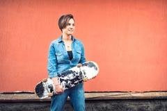 Les jeans de port de fille équipent monter une planche à roulettes, d'isolement sur le fond coloré Concept de mode de vie urbain  Photographie stock