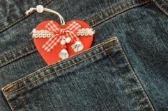 Les jeans donnent une consistance rugueuse avec la poche et le coeur rouge de Noël dans lui Images libres de droits
