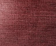 Les jeans donnent une consistance rugueuse dans la couleur rouge Image stock