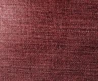 Les jeans donnent une consistance rugueuse dans la couleur rouge Photos stock