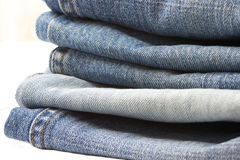 Les jeans empilent sur le blanc Photos stock