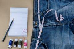 Les jeans et la bande de mesure, aiguille, beaucoup colorent des fils, le bloc-notes, p Photographie stock libre de droits