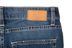 Les jeans halète avec la poche et l'étiquette-vieux fond en bois en cuir brun photographie stock