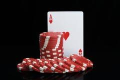 Les jetons de poker ont empilé et des cartes pour jouer sur un fond noir image libre de droits