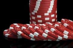 Les jetons de poker rouges ont empilé en gros plan sur un fond noir photos stock