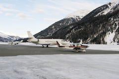 Les jets privés et un propulseur dactylographient l'avion décollant dans l'aéroport de St Moritz Switzerland en hiver Photos stock