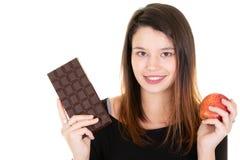 Les jeune beau prises de femme et chocolat ou la pomme rouge de choix ont isolé le portrait blanc de fond dans le studio pour le images stock