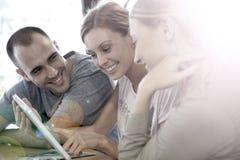 Les jeunes à l'aide d'un comprimé se sont reliés au wifi Images stock