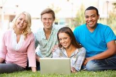Les jeunes à l'aide de l'ordinateur portatif à l'extérieur Photos stock